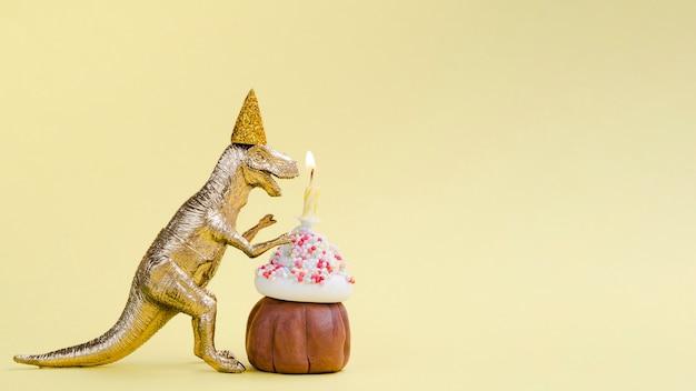 Widok z boku dinozaura i urodzinowy muffin