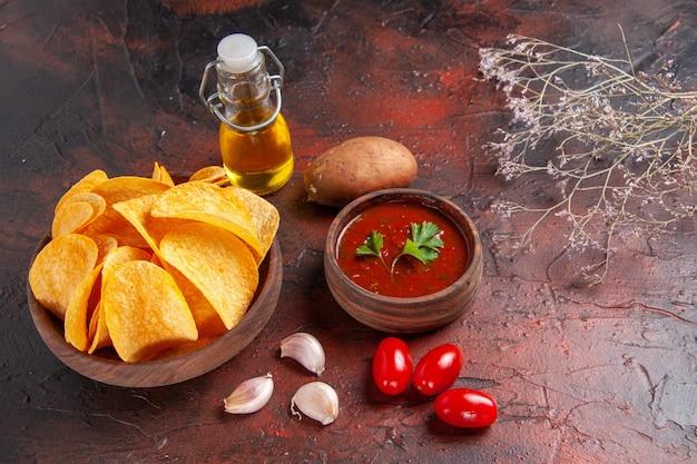 Widok z boku domowych pysznych chrupiących chipsów ziemniaczanych w brązowej butelce oleju ketchup ziemniaki ziemniaczane na ciemnym tle