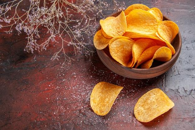 Widok z boku domowych pysznych chrupiących chipsów ziemniaczanych wewnątrz i na zewnątrz brązowego garnka na ciemnym tle