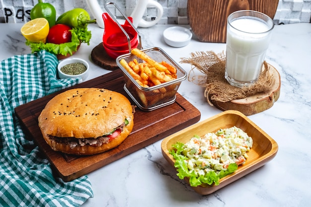 Widok z boku doner kebab z mięsem w chlebie pita na drewnianej desce z sałatką warzywną mieszaną frytki i napój ayran
