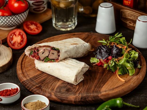 Widok z boku doner kebab zawinięty w lawasz ze świeżą sałatką na desce