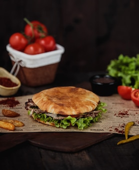 Widok z boku doner kebab ze smażonymi ziemniakami na drewnianej desce do krojenia