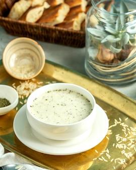 Widok z boku dovga-jogurtowa tradycyjna zupa azerska z ryżem i suszonymi ziołami na tacy