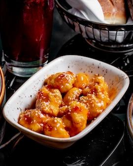 Widok z boku duszona pierś z kurczaka w sosie z sezamem na talerzu
