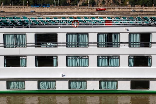 Widok z boku dużego statku wycieczkowego pokazującego główny pokład i leżaki