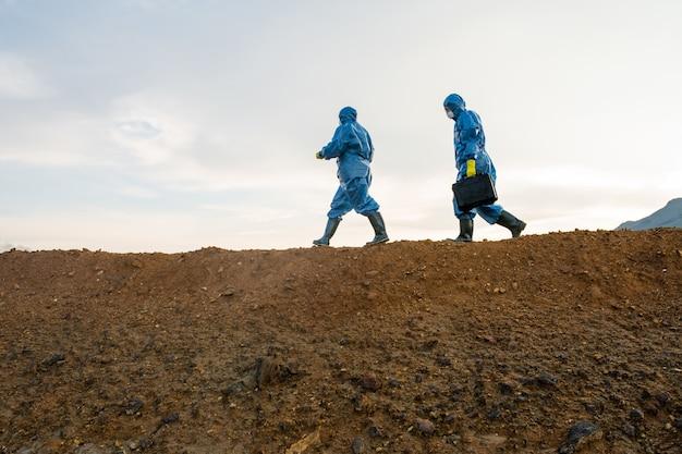 Widok z boku dwóch badaczy w kombinezonach ochronnych poruszających się na szczycie wzgórza z brudną glebą na tle zachmurzonego nieba podczas prowadzenia śledztwa