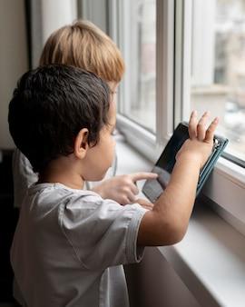 Widok z boku dwóch chłopców grających na tablecie w domu