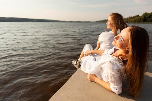 Widok z boku dwóch kobiet podziwiających widok na jezioro