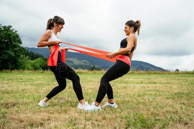 Widok z boku dwóch kobiet wykonujących ćwiczenia siłowe na gumce, wykonujących duży wysiłek w środku lasu