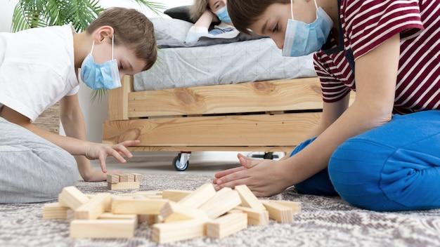 Widok z boku dzieci bawiących się jenga w domu podczas noszenia masek medycznych