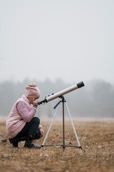 Widok z boku dzieciaka za pomocą teleskopu na zewnątrz