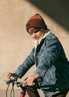 Widok z boku dziecka na rowerze na zewnątrz