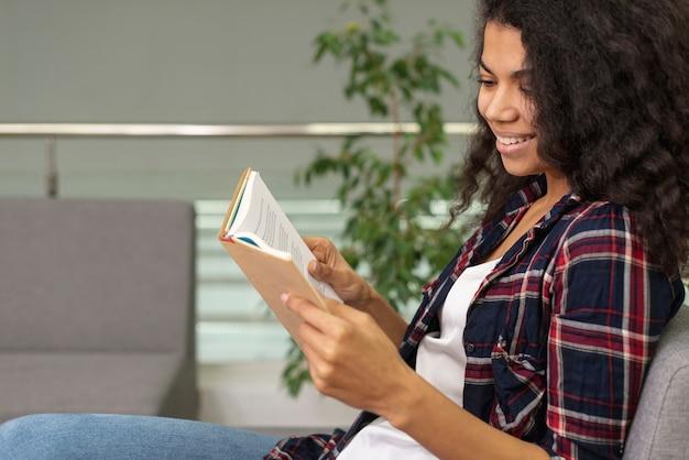 Widok z boku dziewczyna na czytanie fotel
