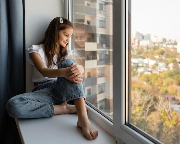Widok z boku dziewczyna patrząc przez okno w domu