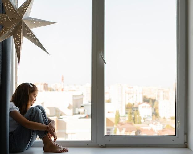 Widok z boku dziewczyna patrząc przez okno