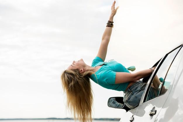 Widok z boku dziewczyna przez okno samochodu