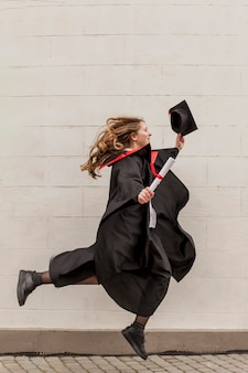 Widok z boku dziewczyna skoki na ukończeniu szkoły