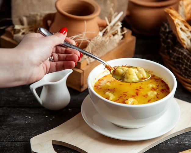 Widok z boku dziewczyna zjada zupę dushbara tradycyjne danie azerbejdżańskie