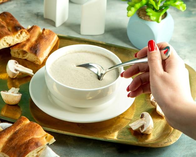 Widok z boku dziewczynka je zupę grzybową z chlebem tandoor na tacy