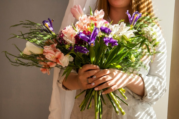 Widok z boku dziewczyny trzymającej bukiet różnych wiosennych kwiatów ciemnofioletowych irysowych kwiatów z alstroemeria, różowych tulipanów, tureckich goździków i fioletowego statice przy lekkim stole