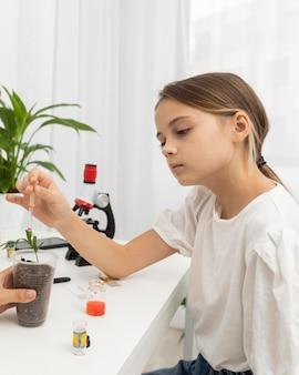 Widok z boku dziewczyny uczącej się nauki z rośliną