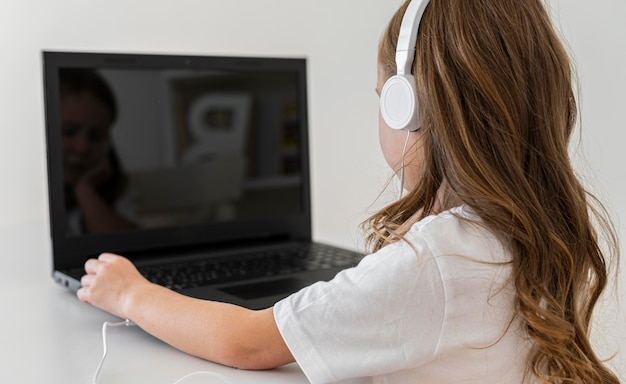Widok z boku dziewczyny za pomocą laptopa ze słuchawkami