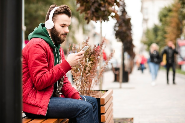 Widok z boku facet ze słuchawkami i smartfonem
