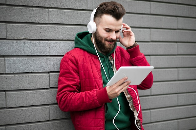 Widok z boku facet ze słuchawkami i tabletem