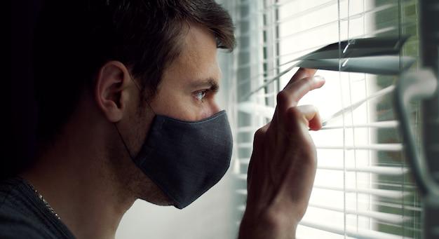 Widok z boku faceta w masce ochronnej patrząc przez okno przez żaluzje, zbliżenie headshot