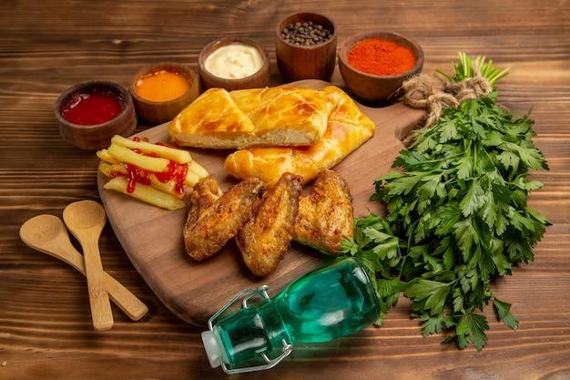 Widok z boku fastfood na desce frytki z ketchupem skrzydełka kurczaka i ciasto na desce obok misek kolorowych przypraw i sosów drewniane łyżki ziół i butelka