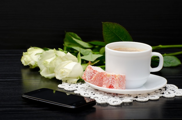 Widok z boku filiżanki kawy z mlekiem, orientalne słodycze. , białe róże na czarnym tle
