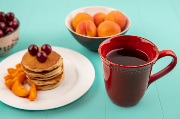 Widok z boku filiżanki kawy z talerzem naleśników i plasterków moreli z wiśniami i miskami wiśni i moreli na niebieskim tle