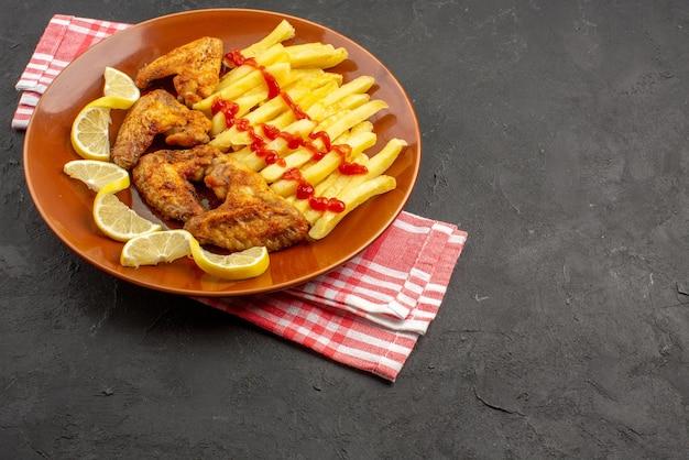 Widok z boku frytki z kurczaka na obrusie w różowo-białą kratkę pomarańczowy talerz z apetycznymi frytkami skrzydełka z kurczaka ketchup i cytryna po lewej stronie ciemnego stołu