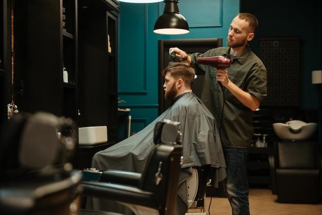 Widok z boku fryzjera za pomocą suszarki do włosów i szczotki do włosów swojego klienta.