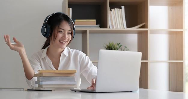Widok z boku głowy strzał uśmiechnięta pani rasy mieszanej w zestawie słuchawkowym, komunikująca się z klientem za pośrednictwem połączenia wideo z komputerem.