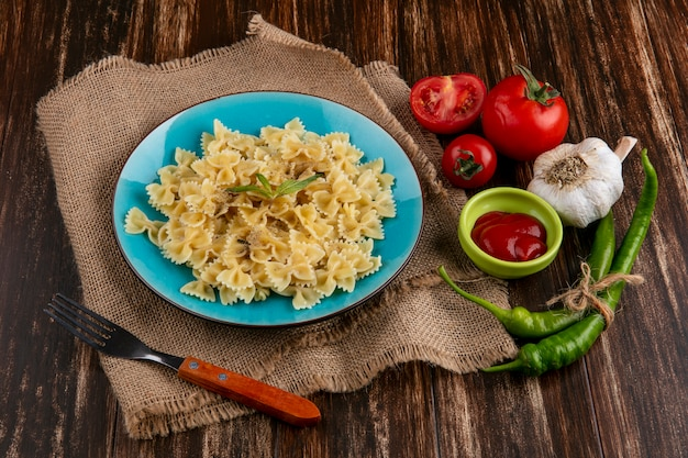 Widok z boku gotowanego makaronu na niebieskim talerzu beżowym serwetce z widelcem pomidory, keczup i papryczki chili na powierzchni drewnianych