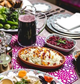 Widok z boku gotowanego ryżu z rodzynkami i jagodami z karafką soku wiśniowego