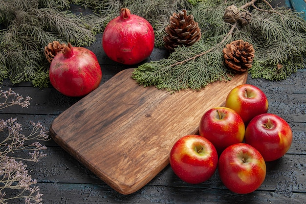 Widok z boku granaty i jabłka dwa dojrzałe granaty obok deski do krojenia pięć jabłek i gałęzi z szyszkami na szarym tle