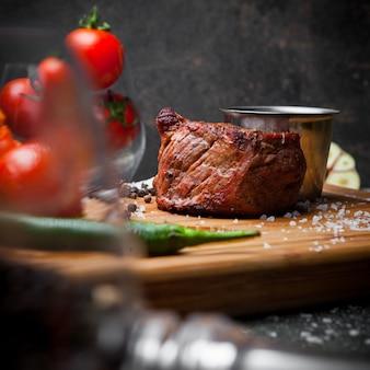 Widok z boku grillowane mięso z pomidorem i sosem w desce stekowej