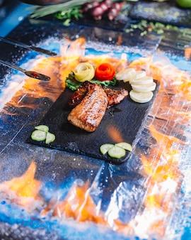 Widok z boku grillowany filet z ryby z cytryną i ogórkiem na tacy
