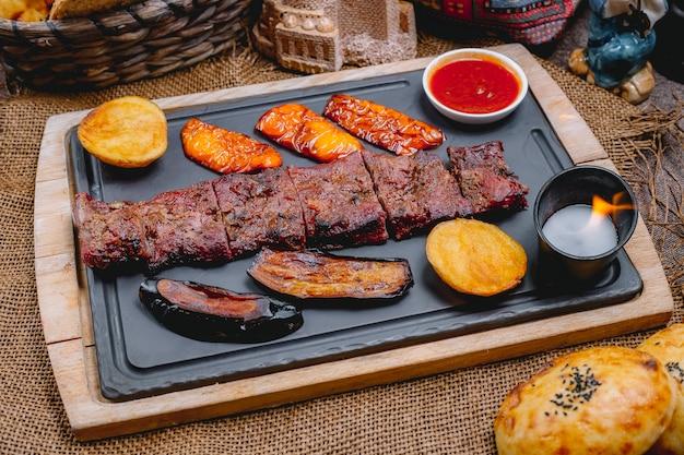 Widok z boku grillowany stek z bakłażanem ziemniaki, sos paprykowy, chleb i świeca na desce