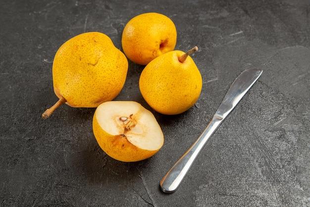 Widok z boku gruszki i nóż trzy żółte gruszki i pół gruszki na ciemnej powierzchni