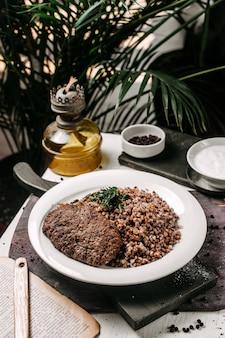 Widok z boku gryki z kotletem mięsnym i ziołami na stole