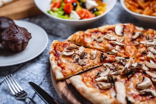 Widok z boku grzybowa pizza z sosem pomidorowym, serem, solą, pieprzem i pieczarkami na desce