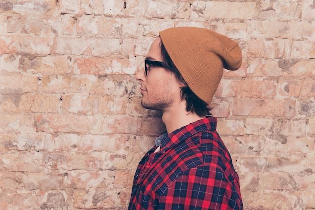 Widok z boku: hipster w kapeluszu w pobliżu ściany z cegły