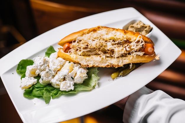 Widok z boku hot dog z kapustą i ziemniakami w majonezie z solonymi ogórkami i sosem