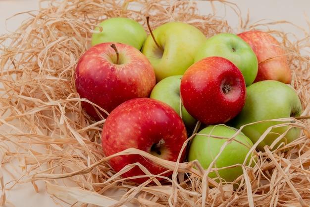 Widok z boku jabłek na słomie na powierzchni kości słoniowej