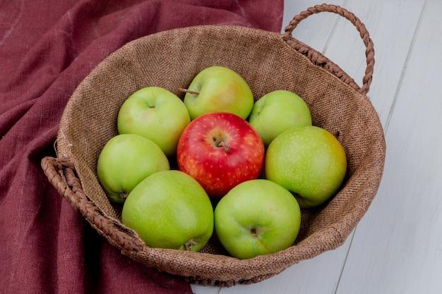 Widok z boku jabłek w koszu na bordo tkaniny i powierzchni drewnianych