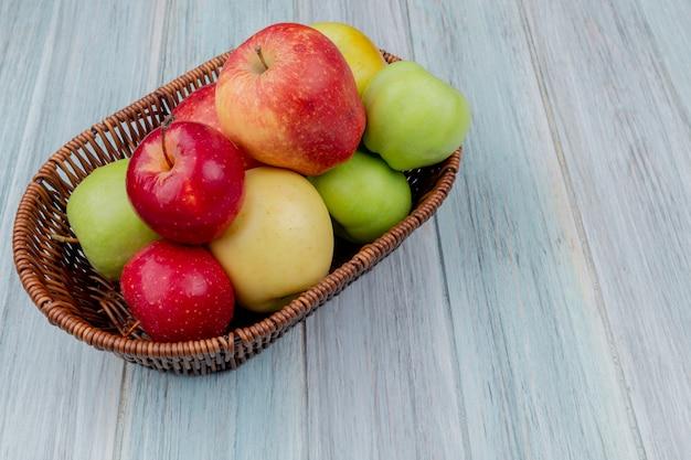 Widok z boku jabłek w koszu na drewniane tła z miejsca kopiowania