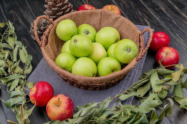 Widok z boku jabłek w koszu z szyszkami i liśćmi na powierzchni tkaniny i drewna